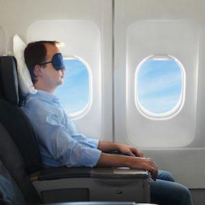 Mann mit Nachtmaske im Flugzeug